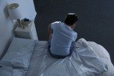 623-05849602 © Masterfile Royalty-Free Model Release: Yes Property Release: No Man sitting on bed
