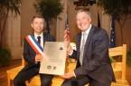 """Städtefreundschaft so fest """"wie eine Bank"""": Châteaurouxs Bürgermeister Gil Avérous und Bürgermeister Henning Schulz auf und mit den Jubiläumsgeschenken. Das Gütersloher Präsent ist ein Gingko-Baum."""
