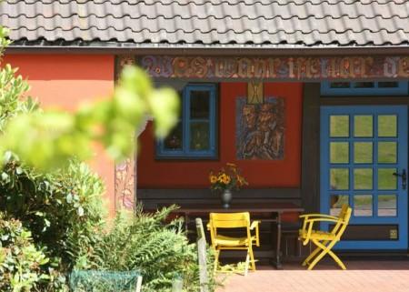 Bunte Idylle im Grünen: Das Böckstiegelhaus besticht durch rote Fassade mit blauen Fensterläden, Copyright: © Peter-August-Böckstiegel-Stiftung