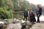 Wasserperlen, die über dem Wasser schweben, aber doch fest verankert sind: Bernd Winkler, Leiter des Fachbereichs Grünflächen, Daniela Toman, Larissa Lakämper (Vorsitzende und Vorstandsmitglied des Förderkreises Stadtpark-Botanischer Garten) und Bürgermeister Henning Schulz stellen die neue Skulptur am Stadtparkteich vor.