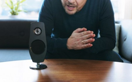 Man sits in his living room and asks a question to his digital assistant placed on a table. The device is connected to the internet and has both a microphone and a speaker. It recieves the questions and provide answers. It can also carry out different tasks as turning on the lights and music at home by voice command.