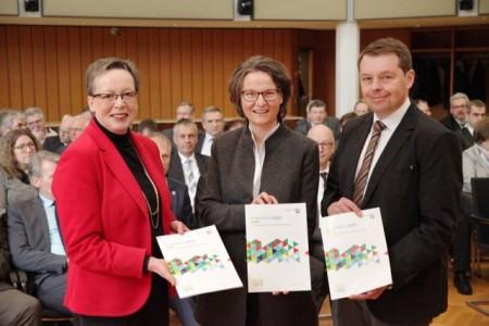 Regierungspräsidentin Marianne Thomann-Stahl (von links), NRW-Kommunalministerin Ina Scharrenbach und Heiner Brockhagen (Geschäftsführer Förderkoordinationsstelle) mit der neuen Förderinformationsbroschüre der Bezirksregierung zur REGIONALE 2022.