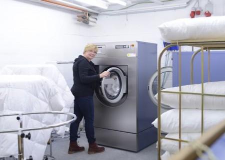 Alles sauber: Ulrike Schramm, Mitarbeiterin von Betten Struve in Lübeck, holt Oberbetten aus der Miele-Waschmaschine. Auf den Ständern neben ihr hängen Steppdecken, die später in den Trockner kommen.