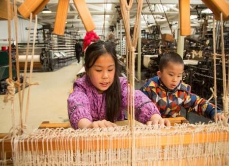 Am Handwebstuhl lernen die Kinder im LWL-Textilmuseum zunächst die Technik des Webens kennen. Foto: © LWL/Betz
