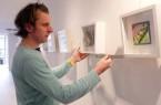 Künstler Joachim Stäbler beim Aufhängen seiner Bilder im Parlamentarischen Bereich des Kreishauses.