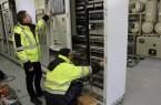 Kornel Witte (rechts) von der Firma Siemens und Hendrik Lohmann von den Stadtwerken Bielefeld kontrollieren die neue Steuer- und Leittechnik. Im Hintergrund sieht man die 110.000 Volt-Schaltanlage im Umspannwerk Kraftwerk.