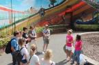 Während der neuen Kiez-Tour geben die beiden Stadtführerinnen von Bielefeld Marketing Janine Vetter (l.) und Yvonne Bock (in pinken Bielefeld-Shirts) Informationen zum auffälligen Graffiti an der Stadtbahn-Unterführung zur Rudolf-Oetker-Halle. Copyright: © Bielefeld Marketing GmbH