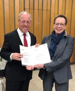 """Bielefelds Oberbürgermeister Pit Clausen freut sich über Städtebaufördermittel in Höhe von etwa 2 Millionen Euro, überreicht von Regierungspräsidentin Marianne Thomann-Stahl. Etwa 1,3 Millionen Euro sind für das """"grüne Klassenzimmer"""" im Halhof in Bielefeld bestimmt."""