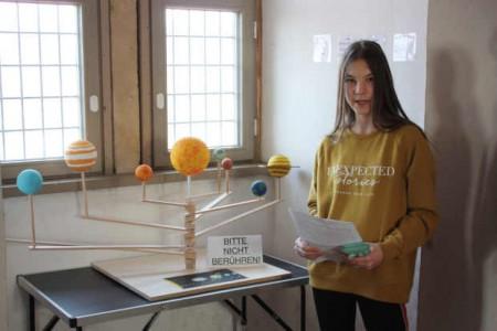 Die Schülerin Cara-Anouk Pfeiffer am selbst angefertigten Planetenmodell. © Weserrenaissance-Museum Schloss Brake