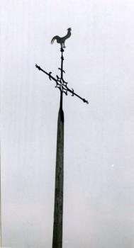 Hagelkreuz in Bocholt-Mussum (zwi-schen 1950 und 1970). An dieser Stelle soll schon in früheren Jahrhunderten ein Hagelkreuz gestanden haben, das 1886 erneuert worden ist. Die Jahreszahl befindet sich in den Schwanzfedern des Wetterhahns. Foto: LWL Volkskundearchiv