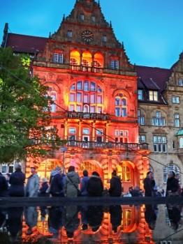 """Bildzeile: """"Für das Rahmenprogramm tauchen die Stadtwerke Bielefeld die Altstadt wieder in ein ganz besonderes Licht, unter anderem am Alten Rathaus, dessen Fassade zu einer interaktiven Videofläche wird."""" Foto: Bielefeld Marketing/Sarah Jonek"""