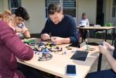 Basteln digital und analog: Bevor die Figuren ihren Weg ins Spiel finden, bauen Gamedesigner  Gregor Assfalg und die Teilnehmer des Workshops Vorbilder aus Lego. Foto: Stadt Gütersloh
