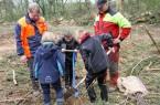 Drei Schüler der OGS Brake pflanzen unter Anleitung der beiden Landesverbands-Forstwirte Rainer  Varenholz (l.) und Andreas Peglow (r.) eine Stieleiche.