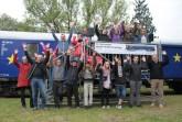 """Begeistert für die Demokratie - Die Organisatoren der U18-Europawahl freuen  sich gemeinsam mit Gästen und """"Jungwählern"""" vor dem als Europaflagge  lackierten Jugendwaggon an der Bahnmeisterei in Farmbeck, Foto: Ilja Nowodworski"""