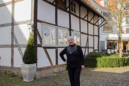 """Stadtführerin Barbara Best empfängt Teilnehmer des Stadtrundgangs """"Mit Hinz und Kunz durch Gütersloh"""" vor dem Stadtmuseum"""