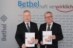 Pastor Ulrich Pohl (r.) und Dr. Rainer Norden mit dem aktuellen BethelJahresbericht 2018/2019. (Foto: Bethel)