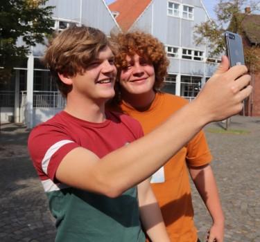 Smartphone gezückt und mithilfe der digitalen Stadtführung viel erfahren – Louis Blawert und Julius Haun haben sichtlich Spaß am digitalen Rundgang durch die Stadt. Foto: Stadt Rheda - Wiedenbrück