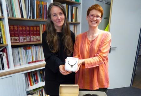Zusammen mit Sonja Voss vom Heimatmuseum Löhne (l.) präsentiert Dr. Julia Hallenkamp-Lumpe von der LWL-Archäologie einen der Reitersporne, die in der neuen Ausstellung im Museum zu sehen sein werden. Foto: LWL/S. Spiong