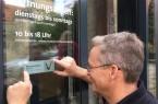 Freudestrahlend bringt der Haustechniker Thomas Senke das Schild an der Eingangstür  des Weserrenaissance-Museums Schloss Brake an. Foto: Schloss Brake