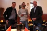 """Arne Brand, Allg. Vertreter der Verbandsvorsteherin/des Verbandsvorstehers, und Jürgen Hoppe überreichen Suar Kassem einen Kochlöffel sowie eine Kochmütze und gratulieren zur Eröffnung von """"El Molino"""". Foto: Landesverband Lippe"""
