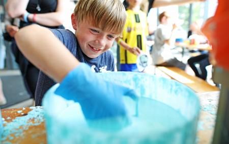 Junge taucht behandschuhte Hand in einen Eimer