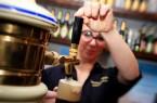Junge Frau zapft Bier vom Fass