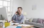 Ein Mann sitzt im Wohnzimmer vor einem Computer und telefoniert