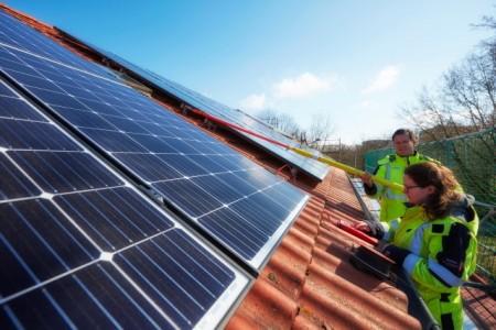 Nicole Vagedes und Thomas Arnold von den Stadtwerken überprüfen die fertiggestellte Photovoltaikanlage am Buchfinkenweg. Foto: Thorsten Ulonska