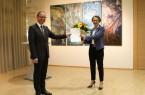 Ministerin Ina Scharrenbach überreicht die Ernennungsurkunde und einen Blumenstrauß an Jörg Düning-Gast, im Hintergrund Werke der ostwestfälischen Künstlerin Rosemarie Sprute.