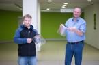 Björn Horstmann (l.) hat über 50 Gesichtsschilder mit dem 3D-Drucker gebaut und diese jetzt an das St. Ansgar Krankenhaus gespendet. Darüber freut sich Hygienefachkraft Jochen Balke.