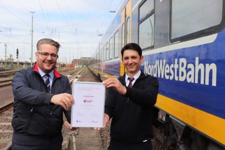 Eduard Skura (rechts) bekommt die Auszeichnung für den Landessieg von Robert Palm, Regionalleiter der Regio-S-Bahn Bremen/Niedersachsen überreicht. Foto: NordWestBahn/Steffen Högemann