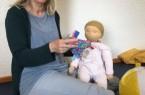 "Mit Puppe und Laptop: PEKiP Kursleiterin Dagmar Lamprecht bei Ihrem Online-Kurs ""PEKiP Digital"". Foto:"