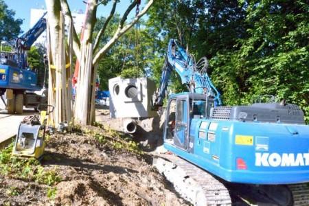 Mit viel Feingefühl musste das rund 25 Tonnen schwere am Autokran hängende Schachtbauwerk mit dem Baggerarm in Position gedreht werden, bevor es abgesetzt werden konnte. Foto: © Stadt Paderborn
