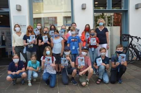 (Auf dem Foto von von links), Koodinatorin des Kulturrucksackes, und Erika Berners-Kaffenberger (rechts), Leiterin der Kinderbibliothek, freuen sich gemeinsam mit den Kindern auf den ersten Testlauf des digitalen Rätselratens.Foto: © Stadt Paderborn