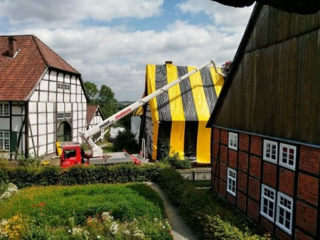 Blick aus Richtung des Gartens am Valepagenhof auf das Haus Stahl, das gerade in die farbigen Folien gehüllt wird. Foto: LWL/Michels