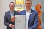 Bürgermeister Theo Mettenborg und Alexander Löhner, Digitalisierungsbeauftragter im Fachbereich Jugend, Bildung und Sport, präsentieren den Förderbescheid.
