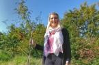 Gut gewachsen: Laura Schuster vom KlimaPakt Lippe mit der Vogelbeere, die der Kreis vergangenes Jahr beim Einheitsbuddeln gepflanzt hat. Foto: Kreis Lippe
