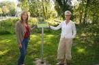 Die Technische Beigeordnete Claudia Warnecke (rechts) freut sich zusammen mit der Landschaftsökologin Lea Heinrichsdorff (Amt für Umweltschutz und Grünflächen der Stadt Paderborn) über die positive ökologische Entwicklung an der renaturierten Pader und ihren Quellen. Zum Schutz der dort lebenden Pflanzen- und Tierarten haben sie Hinweisschilder aufstellen lassen. Foto: © Stadt Paderborn