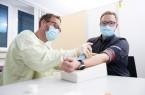 Thorsten Engelking, Mitarbeiter des HDZ NRW (Foto li.), nimmt EDEKA-Mitarbeiter Mario Grotefeld Blut ab für den Antikörpertest.  Foto: EDEKA Minden-Hannover