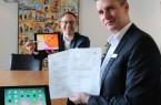 Bürgermeister Theo Mettenborg und Digitalisierungsbeauftragter für den  Bereich Jugend, Alexander Löhner, freuen sich über die Förderzusage und testen das erste  Tablet für die Schülerinnen und Schüler. Foto: Stadt Rheda - Wiedenbrück