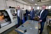 Firmenchef Michael Henkenjohann (l.) vor einer modernen CNC-Drehmaschine. Ihm schauen Bürgermeister Michael Berens, in der Hand eine Traverse für Werkzeuge, und Wirtschaftsförderer Thomas Westhof (r.) zu. Foto: Stadt Hoevelhof