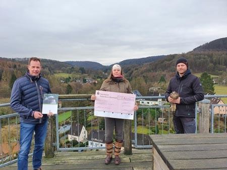 Marie Drawe (Mitte) überreicht den symbolischen Spendenscheck an Klaus Hansen (links) und Benjamin Aschmann (rechts) von der Adlerwarte Berlebeck. Foto: Stadt Detmold