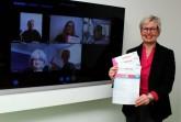 Die Vorbereitungsgruppe hat die Veranstaltungen des Frauenkalenders 2021 digital geplant: Auf dem Bildschirm zugeschaltet sind (v.l. oben) Angela Droste (LWL-Klinikum Gütersloh, Referat für Chancengleichheit), Anja Toppmöller (CDU-Frauen-Union Gütersloh), Bettina Müller-Maiweg (Arbeitslosenselbsthilfe/ASH), (v.l. unten) Ines Böhm (Bündnis 90/Die Grünen Gütersloh) und Dr. Susanne Kohlmeyer (Arbeitslosenselbsthilfe/ASH), den Frauenkalender zeigt Inge Trame (rechts; Gleichstellungsbeauftragte der Stadt Gütersloh).