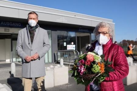 Landrat Sven-Georg Adenauer hat Elisabeth Köhn einen Blumenstrauß geschenkt. Sie ist die 10.000 Person, die ihre Coronaschutzimpfung im Impfzentrum erhalten hat. Foto: Kreis Gütersloh
