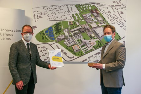 ICL-Geschäftsführer Jörg Rodehutskors (r.) überreicht Verbandsvorsteher Jörg Düning-Gast das Mitgliedszertifikat und das ICL-Display vor dem perspektivischen 3D-Lageplan des ICL. (Foto: LVL)