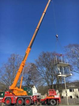 Am Teleskopkran hängt ein Wartehäuschen, bereit für den Aufbau an der Bushaltestelle des Impfzentrums an der Marienfelder Straße. Foto: Kreis Gütersloh