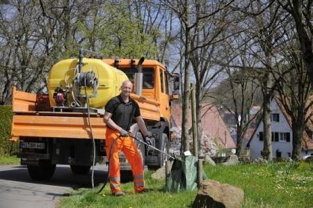 Sieht aus wie Gießen, ist es auch, aber nicht nur: Stadtgärtner Axel Wellmann bewässert einen jungen Baum nahe des Schützenplatzes mit einer speziellen Nährstofflösung, um ihm auf die Sprünge zu helfen.Foto:Stadt Lübbecke