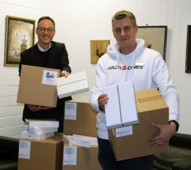 v.l.: Bürgermeister Theo Mettenborg und Alexander Löhner (Digitalisierungsbeauftragter Fachbereich Jugend, Bildung und Sport) nehmen die Lieferung der 1.125 IPads entgegen.