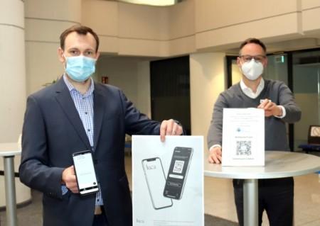 v.l.: Daniel Wiens, Abteilungsleiter Organisation und Zentraler Service, und Bürgermeister Theo Mettenborg testen den QR-Code der Luca-App im Rathausfoyer.