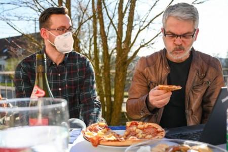 Begeisterung sieht anders aus. Mit seelischer Unterstützung von René Meistell (l.), verspeiste Professor Dr. Carlo Masala (r.) eine Pizza Hawaii. Foto: Christian Weische